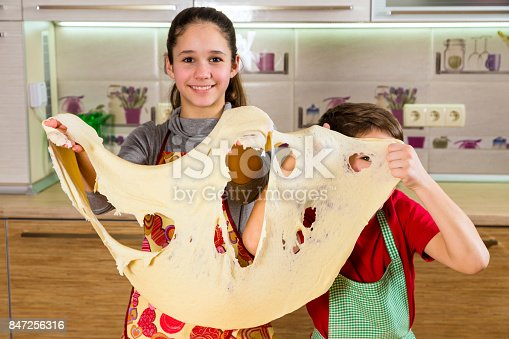 488109116istockphoto Two funny kids with thin dough sheet, making the pizza 847256316