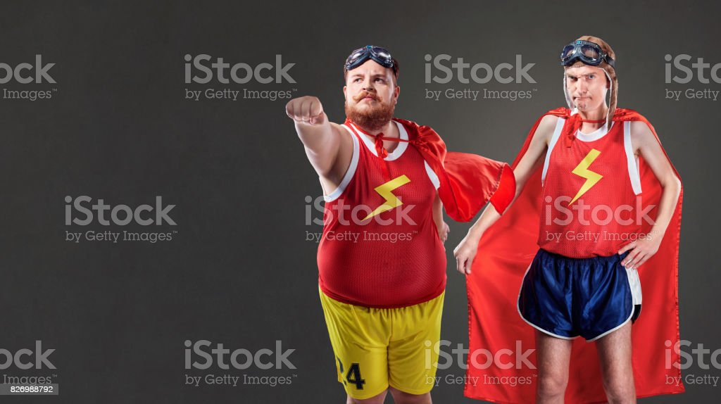 Two funny men in suits of superheroes. Thin and fat people stock photo
