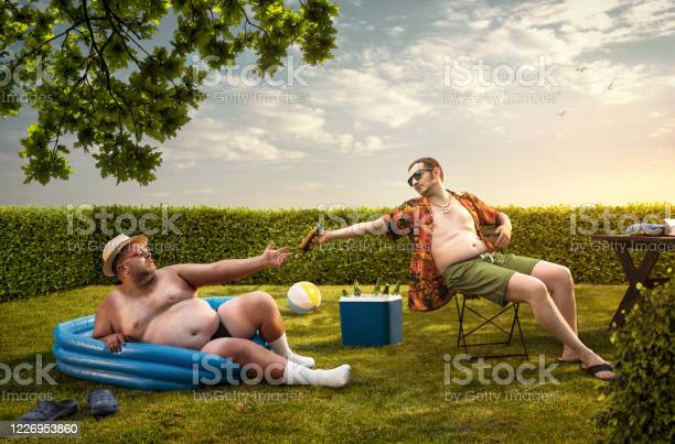 Photo of Two funny nerds relaxing in the backyard on the summer day