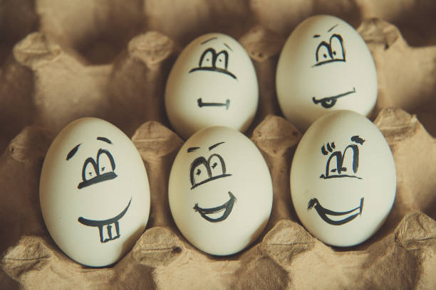 two funny smiling eggs in a packet. - sad cartoon images stock photos and pictures