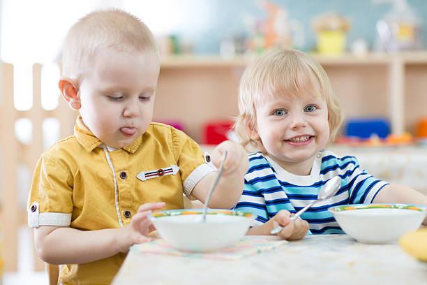 zwei lustige lächelnde kleine kinder bereits im kindergarten essen in - quarkspeise stock-fotos und bilder