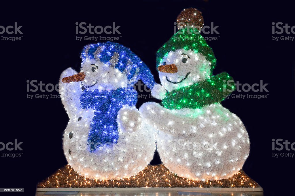 Two funny snowman wave against black night background royalty-free stock photo