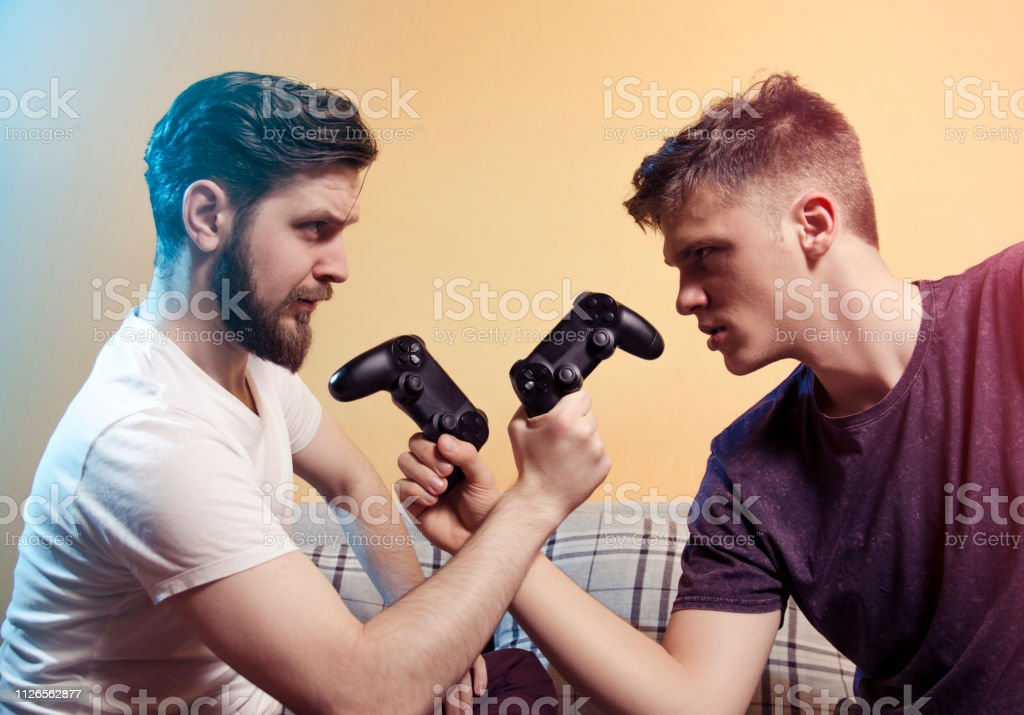 Two gamers head to head, red and blue player with game controllers,...
