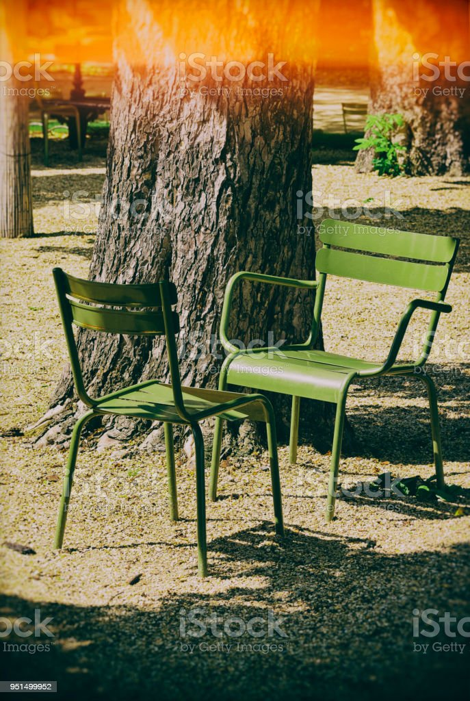 Two classic metal garden chairs in a public park in Paris, France