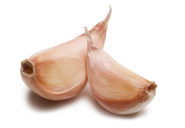 Two garlic cloves isolated on white background. stock photo