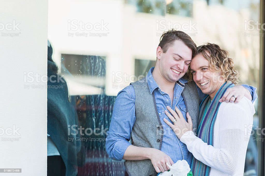 Two gay men shopping, hugging stock photo