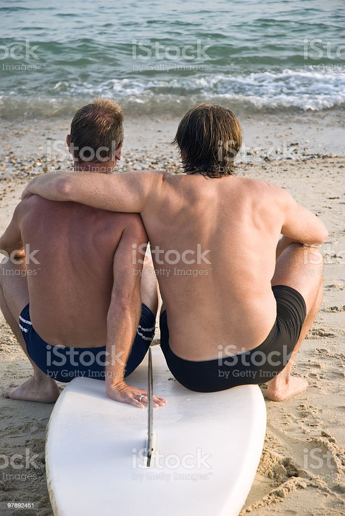 Two gay men sitting on surfboard stock photo