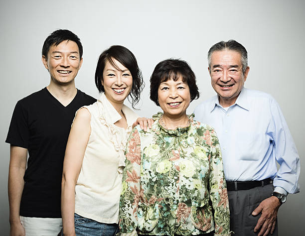 Two generation japanese family Studio portrait of a japanese or asian two generation family. 4 members: old parents and mid age son and daughter. Horizontal color image from a medium format digital camera. Sharp focus on eyes. old mother son asian stock pictures, royalty-free photos & images