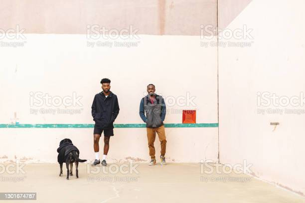 Two Generation Z Males Having Fun And Messing Around On A Hand Ball Court With Pet Dog Photo Series Stock Photo - Download Image Now