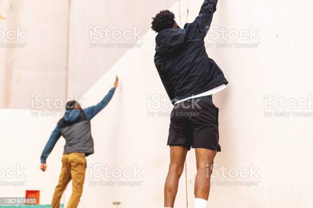 Two Generation Z Males Having Fun And Messing Around On A Hand Ball Court Photo Series Stock Photo - Download Image Now