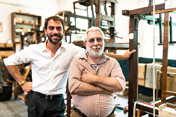 two generations Industrial owner inside their factory stock photo