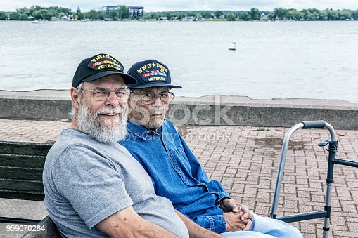Two generations of real person senior adult men USA military war veterans are sitting together sightseeing at the lake. On the right, a 95 year old United States Army World War II and Korean Conflict US Air Force military veteran - on the left, his son-in-law - a 67 year old US Navy Vietnam War military veteran. Canandaigua Lake, in the Finger Lakes region near Rochester, in western New York State.  They are both wearing inexpensive, non-branded, generic, souvenir shop replica military veteran commemorative baseball style caps.  NOTE: There are no official or authentic military uniform elements of any kind in this image - and no intent to portray anything other than proud and patriotic, authentic United States military war veterans.