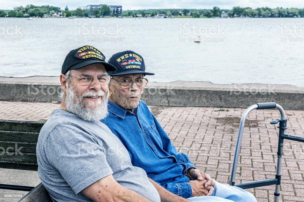 Zwei Generationen von Senioren Erwachsene USA Militärveteranen sitzen am See – Foto