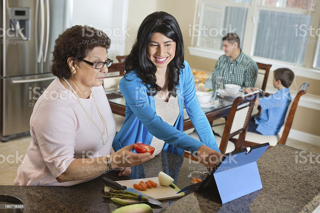 Two generations women using tablet device for recipe in kitchen royalty-free stock photo