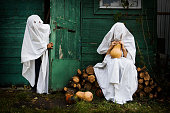 istock Two Ghost covered with a white ghost sheet with pumpkins in an autumn garden for Halloween party. Halloween Concept. 1180204435