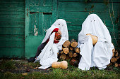 istock Two Ghost covered with a white ghost sheet with pumpkins in an autumn garden for Halloween party. Halloween Concept. 1180204446