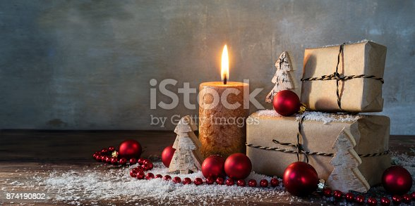istock two gift boxes and a burning candle, red christmas baubles and small wooden toy trees in some snow on rustic wood, vintage background with large copy space, panorama format 874190802