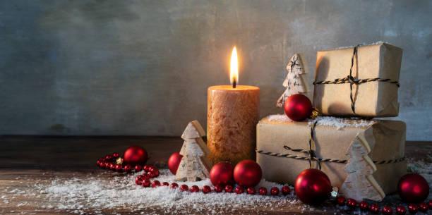 zwei geschenk-boxen und eine brennende kerze, rote christbaumkugeln und kleine holzspielzeug bäume im schnee auf rustikalen holz, vintage-hintergrund mit großen textfreiraum, panoramaformat - holzdeko weihnachten stock-fotos und bilder