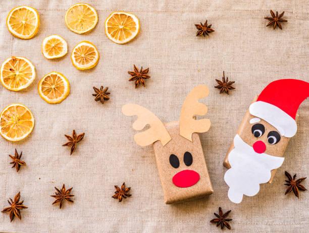 zwei geschenkboxen aus recyceltem papier auf leinen hintergrund mit zitrone und gewürzen. ökologische weihnachten - eco bastelarbeiten stock-fotos und bilder