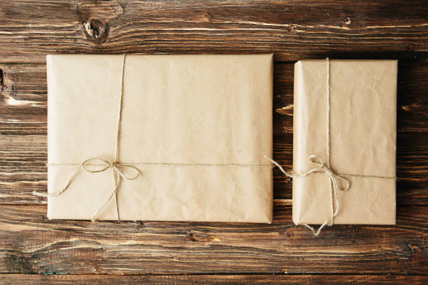 Two gift boxes wrapped in kraft paper on wooden table stock photo
