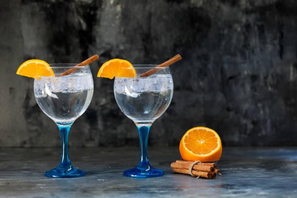 Dos Gin tónicos en cristal azul con canela y naranja - foto de stock