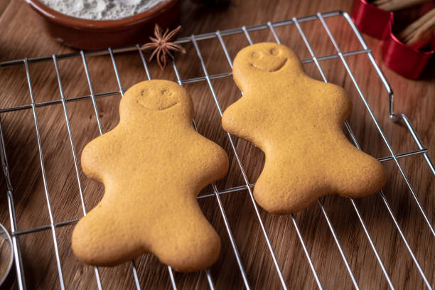 two gingerbread characters on a wire rack - christmas stock photos and pictures
