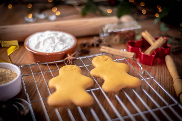 two gingerbread characters on a wire reack - christmas stock photos and pictures