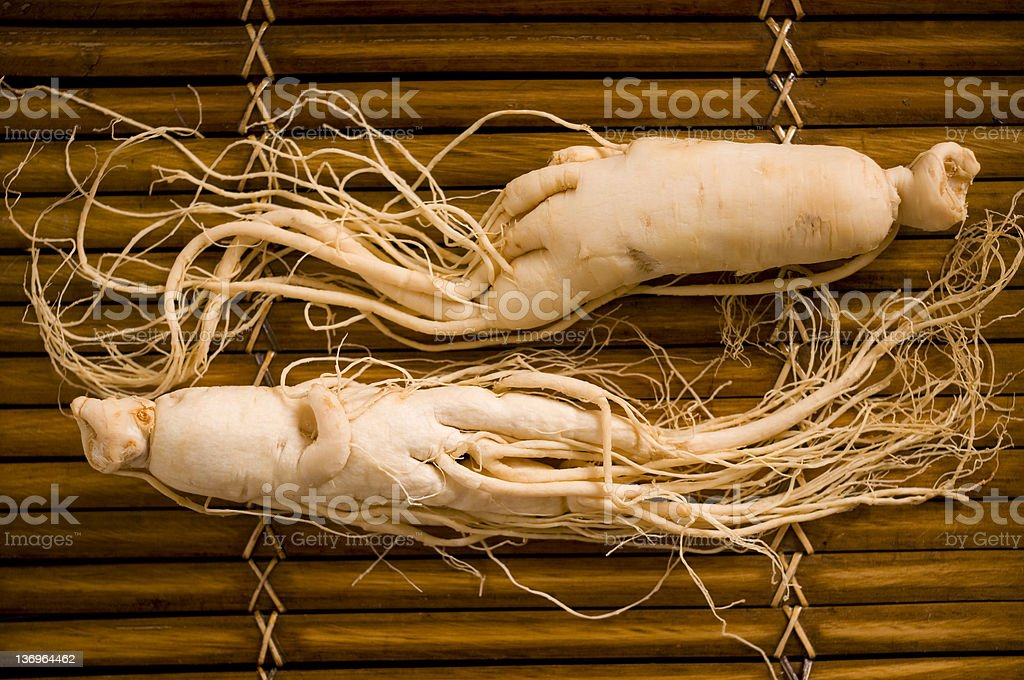 Two ginseng roots on a bamboo mat royalty-free stock photo
