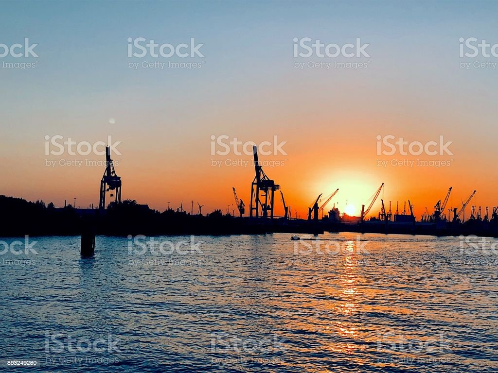 Two giraffes at sunset, cranes at the harbor II stock photo