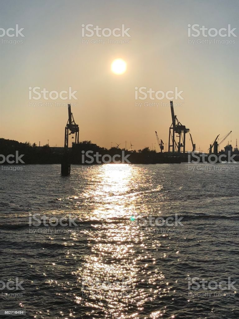 Two giraffes at sunset, cranes at the harbor III stock photo