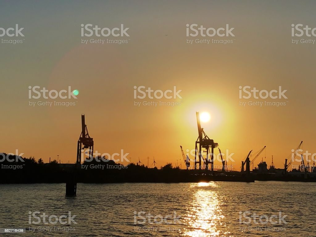 Two giraffes at sunset, cranes at the harbor stock photo