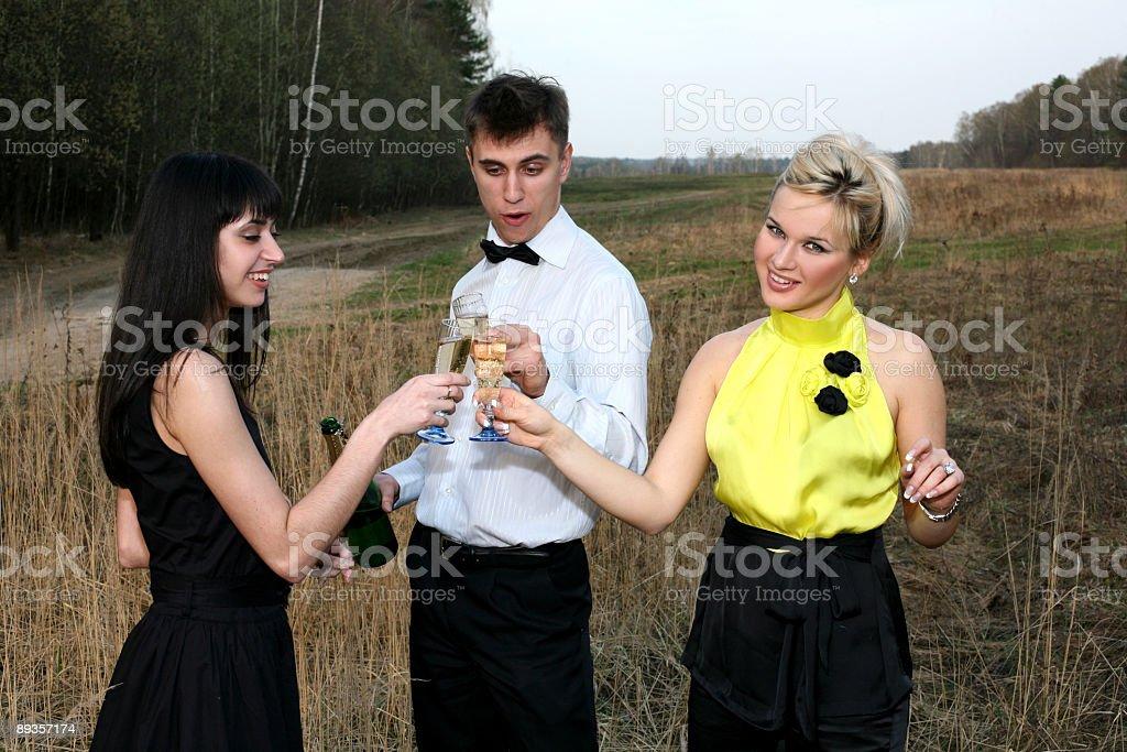 Due ragazza e uomo con una bottiglia di vino all'aperto foto stock royalty-free