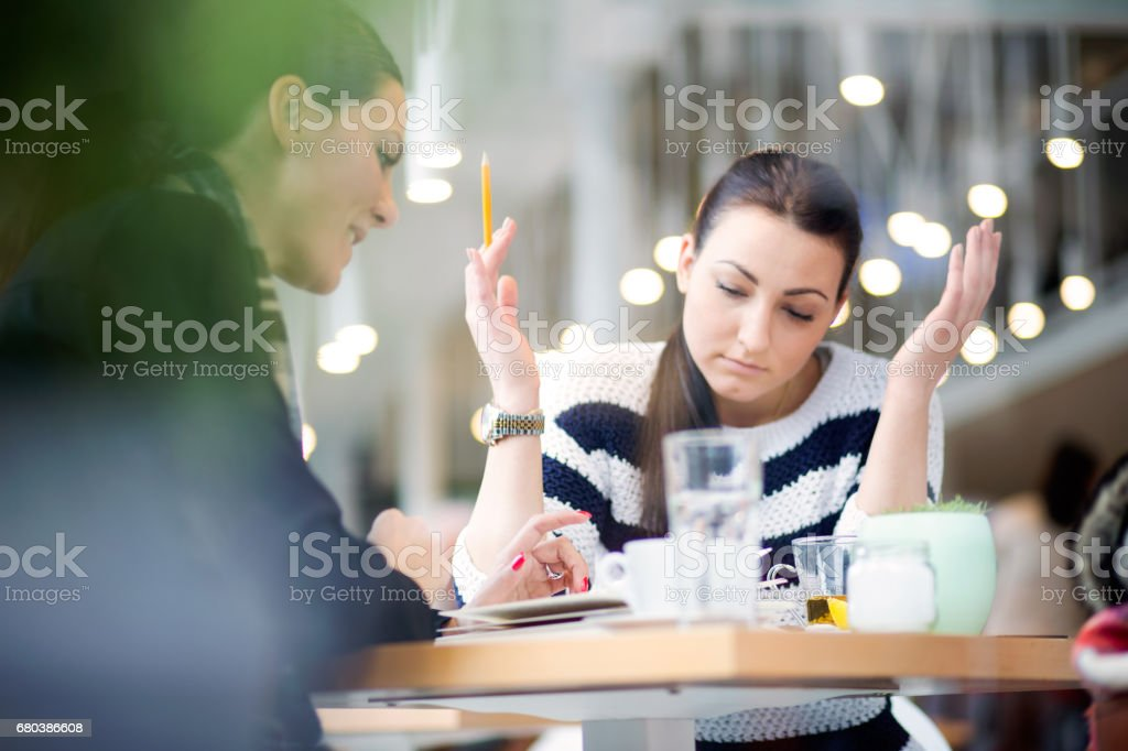 Two girl enjoy a coffee break and studying together royalty-free stock photo