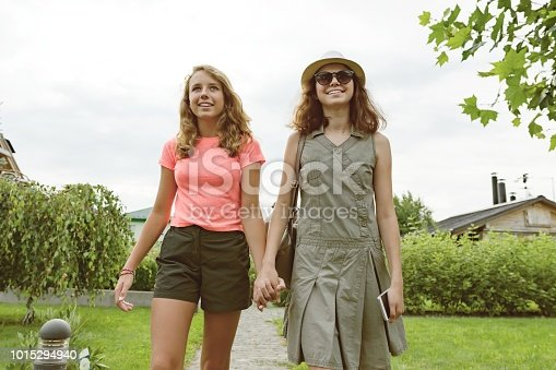 623358818 istock photo Two girl friends go holding hands, background lawn path near the house. 1015294940