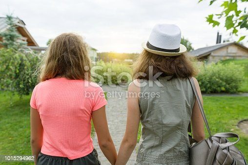 623358818 istock photo Two girl friends go holding hands, background lawn path near the house. Back view. 1015294962