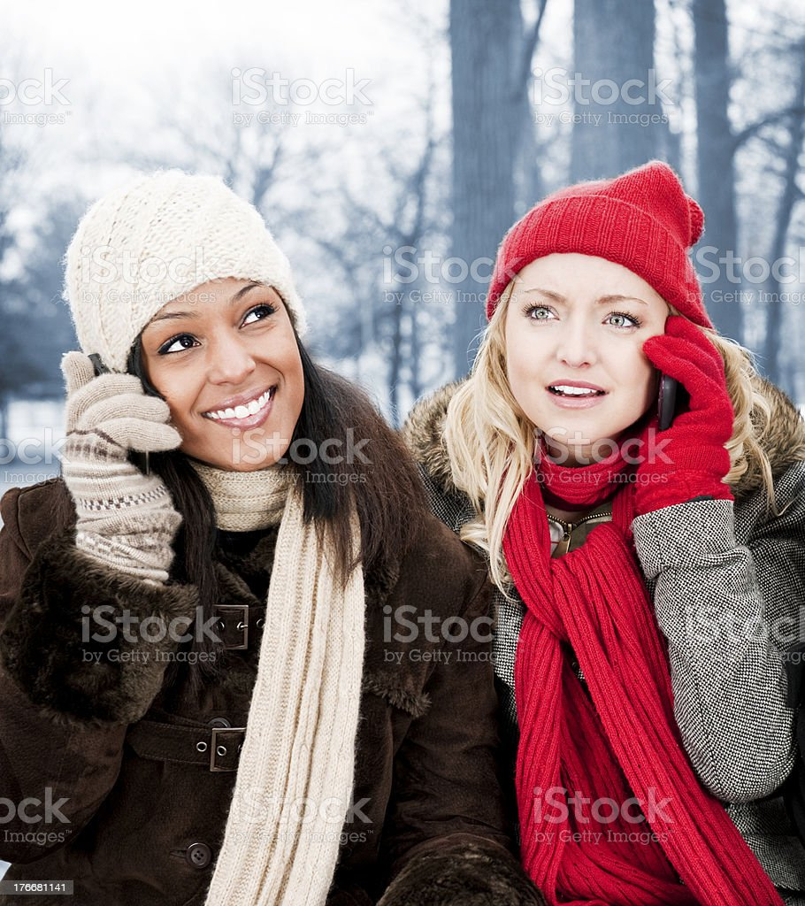 Two girl friends on phones outside in winter royalty-free stock photo