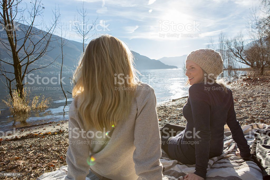 Two girl friends relaxing by the lake stock photo