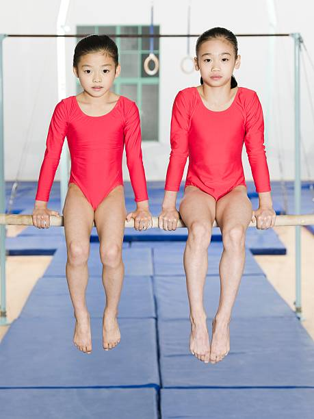 two girl gymnasts - uneven parallel bars stock photos and pictures