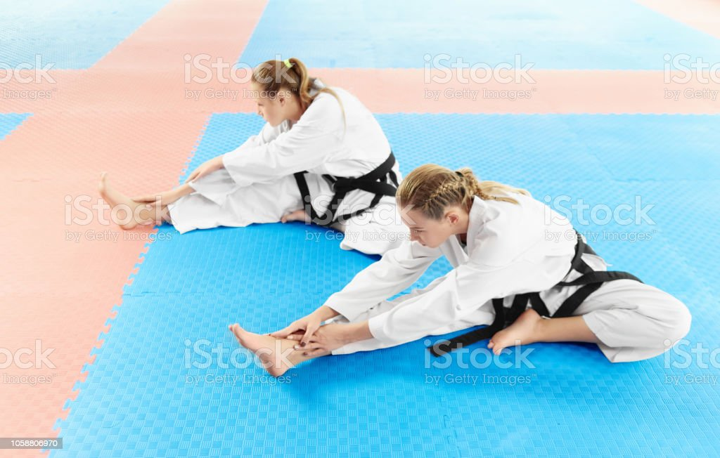 Two girl wearing in white kimono and black belts, training their...