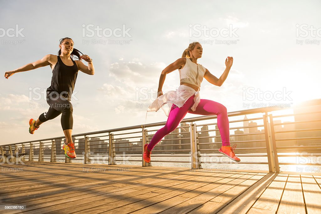 Two girl working out in the park by the bay stock photo