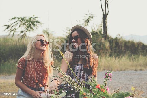 istock Two girlfriend and bike with flower basket 698212430