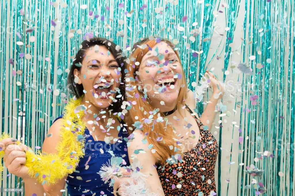 Two girlfriends celebrating the Carnaval and wear colorful scarf. Rain of confetti. The girls are having fun and giggling.'n stock photo