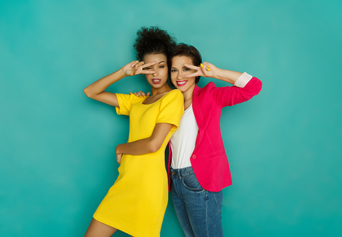istock Two girlfriends fooling and dancing at turquoise studio background 892726482