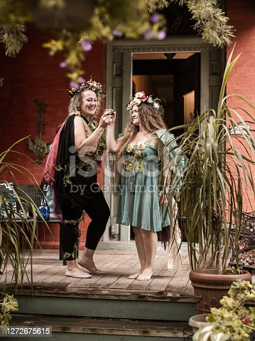 Couple of women dressed in fairy costumes having a glass of wine together.  Front stoop Exterior of beautiful back yard garden.