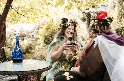 Couple of women dressed in fairy costumes having a glass of wine together.  Table with chairs Exterior of beautiful back yard garden.