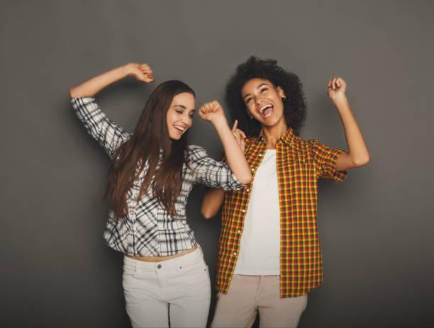zwei freundinnen, die spaß am studio-hintergrund - zum totlachen stock-fotos und bilder