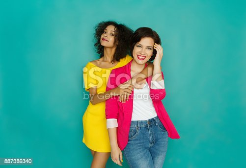 istock Two girlfriends having fun at turquoise studio background 887386340