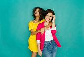 istock Two girlfriends having fun at turquoise studio background 887386340