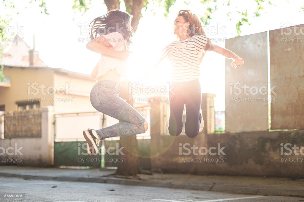 two girlfriends having fun , jumping enjoying stock photo
