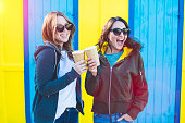 istock Two girlfriends having fun together, drinking coffee to go, during sunset, on a colourful background 1159565483